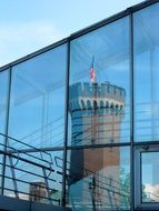mirror image of a tower in a glass facade