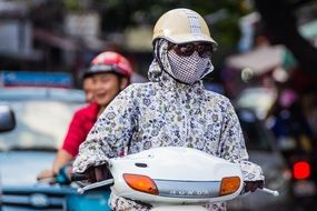 girl in a helmet and a mask on a scooter in Hanoi