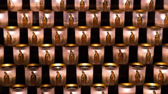 rows of burning candles in painted bowls, france, paris, Notre Dame Cathedral