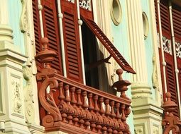 red shutters on Window with balcony, old house Facade
