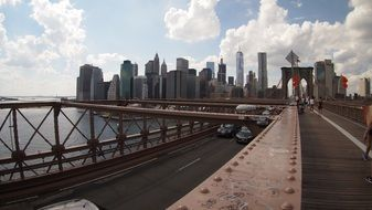 cars drive along brooklyn bridge to new york