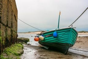 green wooden boat on the shore