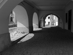 black and white photo of arched architecture in the old town