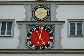 red clock on the facade of the building