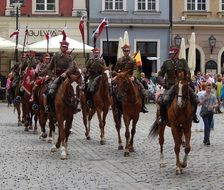 people riding horses with flags in poland
