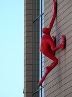 modern red sculpture on a building wall