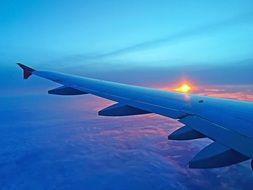 the sun is in the sunset behind the wing of the plane