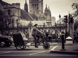 Black and white photo of a cyclist in city traffic at background with the buildings