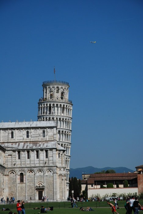 leaning tower behind a building in pisa under a blue sky