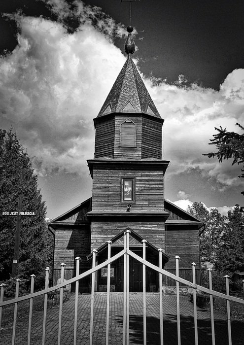 black and white photo of the church behind the fence