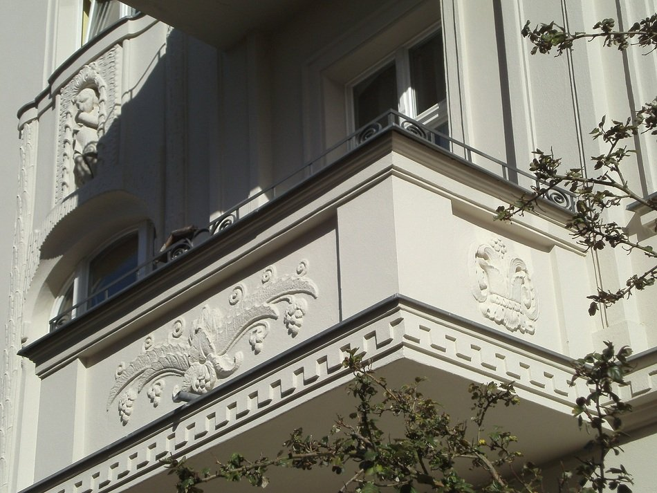 facade of a building with a balcony with stucco