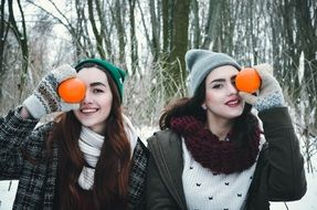 young models in the winter forest posing with oranges