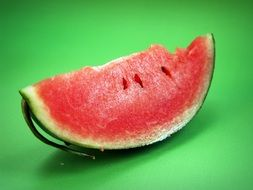 a piece of watermelon on a green background