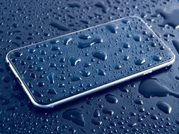 Iphone and black surface in water drops