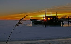 frozrn fishing boat on the lake in winter