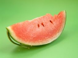 a slice of pink watermelon on a green background