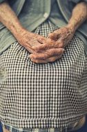 the hands of an elderly woman are folded on their knees