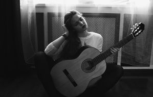 black and white photo of a girl with a guitar in her hands