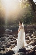 girl in a wedding dress on a rocky bank of a river