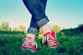 legs in jeans and red sneakers