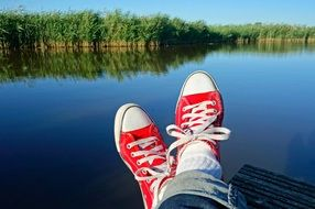 legs in red sneakers on the background of the lake