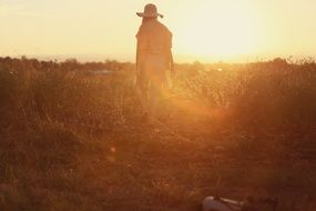 photo of a girl in a straw hat on a rural field at sunset