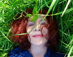 happy girl lying on green grass