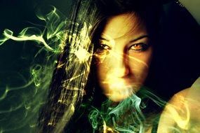 Sorceress, face of dark haired woman behind colorful smoke, collage