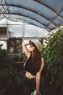 Girl in a greenhouse with green plants