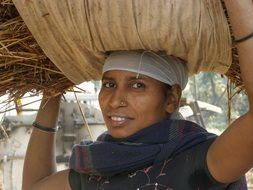 indian woman carries hay on her head