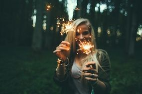 portrait of blonde hair women with fireworks in her hands
