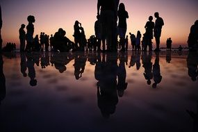 people are reflected in the water
