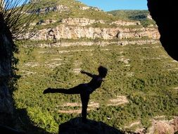 silhouette of a girl in a yoga pose in the mountains