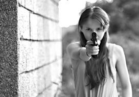 girl aiming a gun black white photo