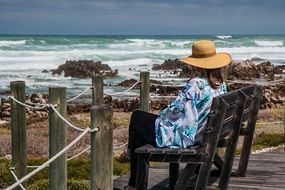 woman sitting on a bench on the coast