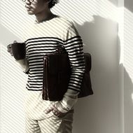 young man in a striped sweater with a case and a cup of coffee