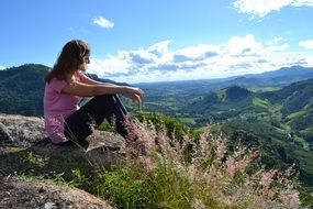 girl in a pink t-shirt on top of a mountain