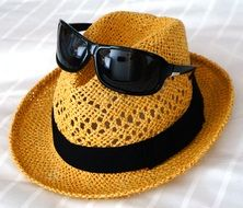 sunglasses on top of a straw hat