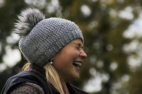 laughing girl in a gray knitted hat