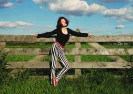 girl in striped pants posing near the fence