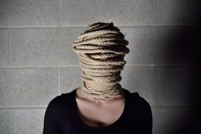 girl's head covered with rope