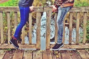 legs of a couple in love on the railing of a wooden bridge