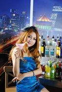 attractive young asian girl sits in bar with cocktail in hand