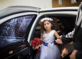 little girl in a white dress coming out of a limousine