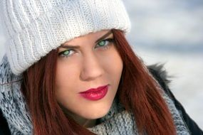 girl with red hair in a white hat in winter