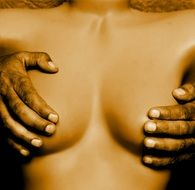 dark skin man's palms on breasts of caucasian Woman