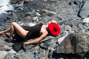 girl lies on stones in a red hat
