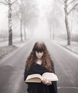 young long haired Girl with Book on Fogg Winter Road