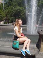 happy girl sitting by the fountain in New York, United States