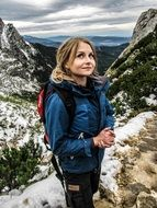 woman in a blue jacket actively travels in the mountains
